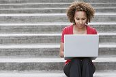stock photo of brunete  - Young African American woman using laptop on steps outdoors - JPG