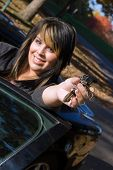 stock photo of car key  - A young girl happily shows off the keys to her new car - JPG