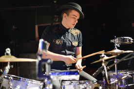 stock photo of bonaparte  - Handsome young man in hat plays drum set in night club - JPG