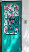 pic of scrollwork  - An ornate door of agua metal and pink scrollwork flowers - JPG