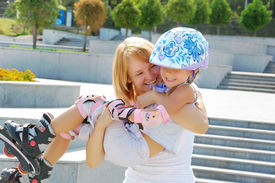 pic of inline skating  - daughter and mother having fun on inline skates in the park - JPG