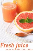 Half of grapefruit, glass of fresh juice and spoon on plate on light background