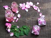 Rose oil in bottles on color wooden background