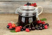 Tasty jam with berries in glass jar on wooden table