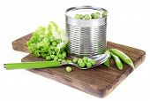 Fresh peas and tin on wooden board, isolated on white