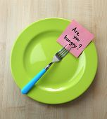 Note paper with message  attached to fork, on plate, on wooden background