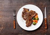 Grilled T-bone Steak  With Vegetables On White Plate On Dark Wooden Background
