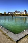stock photo of chateau  - View of the Chateau de Fontainebleau and its reflection across a tranquil lake - JPG
