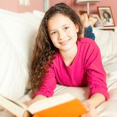 An image of a girl with a book on the sofa