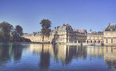 View of the Chateau de Fontainbleu and its reflection across a tranquil lake, situated close to Pari