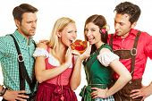 Two women in Bavaria eating a pretzel in front of their jealous men