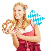 Happy blond woman with pretzel and bavarian flag for the Oktoberfest