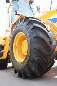 The big yellow wheel of heavy tractor