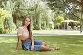 Full length portrait of beautiful young woman relaxing in park