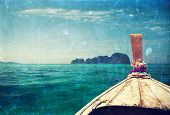 Vintage holiday background - traditional longtail boat heading to an island