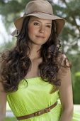 Portrait of trendy young woman wearing sunhat in park
