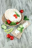 Tasty crispbreads with vegetables on wooden background