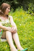 Cute thoughtful young woman relaxing in field