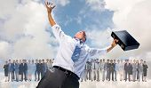 Businessman holding briefcase and cheering against blue sky with white clouds
