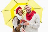 Attractive young couple in warm clothes holding umbrella and leaves on white background