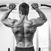Rear view of a male body builder doing pull ups at the gym