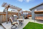 stock photo of grass area  - House backyard with juacuzzi small patio area and garden swing - JPG