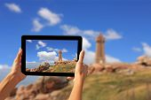 image of por  - Girl taking pictures on a tablet Pors Kamor lighthouse Ploumanac - JPG