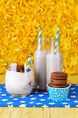 Milk cocktails in glasses and chocolate cookies on yellow background