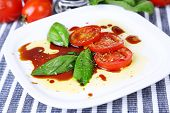 Balsamic vinegar,  tomato and basil on table close-up