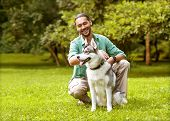 stock photo of husky  - Man and Husky dog walk in the park - JPG