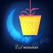 Hanging yellow gift box with shiny blue crescent moon for Muslim community festival Eid Mubarak cele