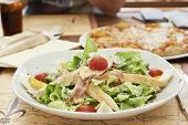 Caesar salad with chicken, smoked ham, eggs and tomatoes