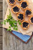 Eight Small Homemade Blueberry Pies On Wooden Table From Top.