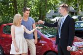 Salesman Giving Key To Couple By Car