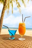 Two Fresh Cocktail On A Beach Under Palm Tree