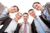 foto of huddle  - Low angle portrait of confident business team making huddle against white background - JPG