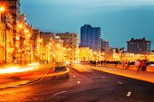 image of malecon  - Sunset in Old Havana with  the street lights of El Malecon and light trails from the passing cars - JPG