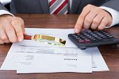 Businessman Calculating Invoice While Holding Magnifying Glass