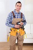Repairman Holding Drill Machine In Living Room