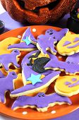 Happy Halloween Orange And Purple Sugar Cookies In Cat, Hat, Bat And Pumpkin Shapes On Orange Polka