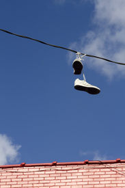 pic of prank  - Unrecoverable shoes hanging over a wire by its tied shoelaces thrown up there as a prank - JPG