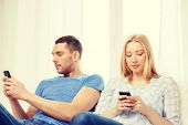 love, family, technology, internet and happiness concept - concentrated couple with smartphones at home