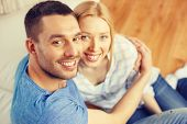 love, family and happiness concept - smiling happy couple at home