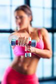 Young fitness woman in pink clothing do exercises with dumbbells in modern interior on windows background. Focus on hand with dumbbell.