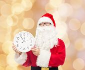 christmas, holidays and people concept - man in costume of santa claus with clock showing twelve over beige lights background