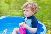 Adorable Blond Toddler Boy Playing With Water, Outdoors.