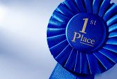 picture of rosettes  - Blue 2nd place winners rosette or badge with a pleated ribbon and gold lettering close up view over white with copyspace - JPG