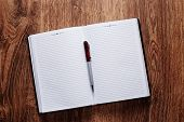 Pen On Blank Open Notebook Placed On Wooden Table