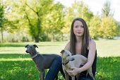 Girl  With Two Greyhounds sitting in park