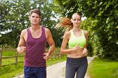 Couple On Run In Countryside Together